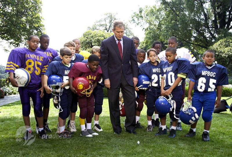 جروج بوش رئیس جمهور امریکا برای شروع بازی بین دو تیم فوتبال خردسال در محوطه کاخ سفید شیر و خط می کند. 9 سپتامبر 2001