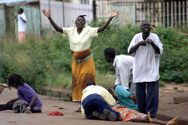 """یک زن پس از شلیک نیروهای امنیتی در شهر """"جوز"""" نیجریه در حالیکه دیگران سعی در کمک به زن مجروح می کنند، دستانش را بلند کرده و فریاد می زند؛ خشونت بین مسیحیان و مسلمانان در مرکز نیجریه در این تاریخ تشدید شده است. 9 سپتامبر 2001"""