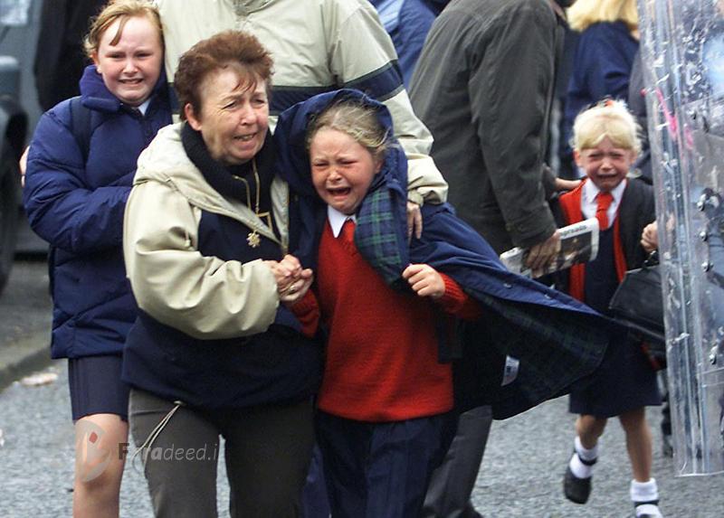 """کودکان و والدین وحشت زده پس از انفجار یک بمب در جاده شمال """"بلفاست"""" در ایرلند. 5 سپتامبر 2001"""